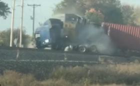 Шофьор изскача от кабината на влекач секунди преди удар с влак (Видео)