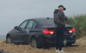 Малшанс: Човек се заключи извън колата си, докато тя буксува в пясъка! (Видео)